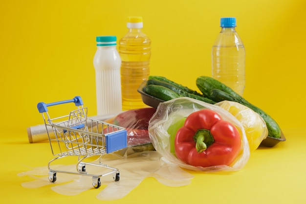 Shopping trolley and food in plastic packaging on yellow background copy space