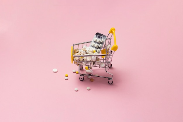 Shopping trolley from the supermarket full of pills and drugs on a pink background. purchases of medical preparations, purchase on the internet.