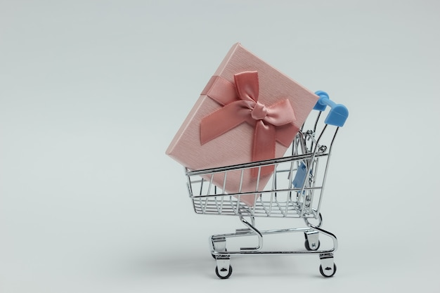 Shopping trolley and gift box with bow on white background. composition for christmas, birthday or wedding.