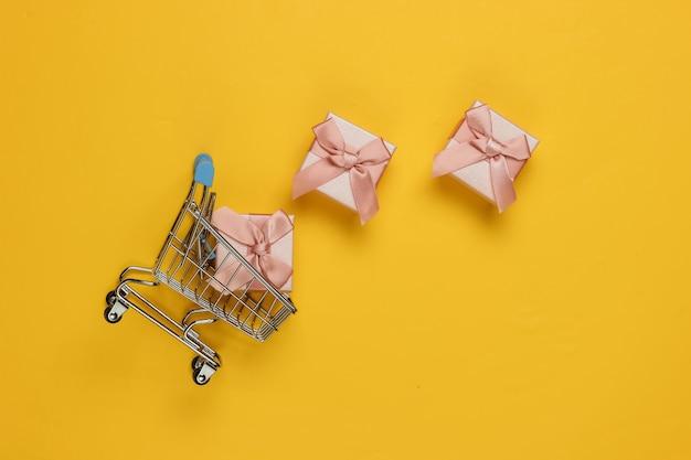 쇼핑 트롤리, 노란색 바탕에 리본으로 선물 상자. 크리스마스, 생일 또는 결혼식을위한 구성. 평면도