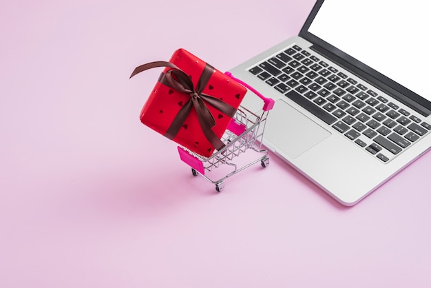 Shopping trolley and gift near modern laptop