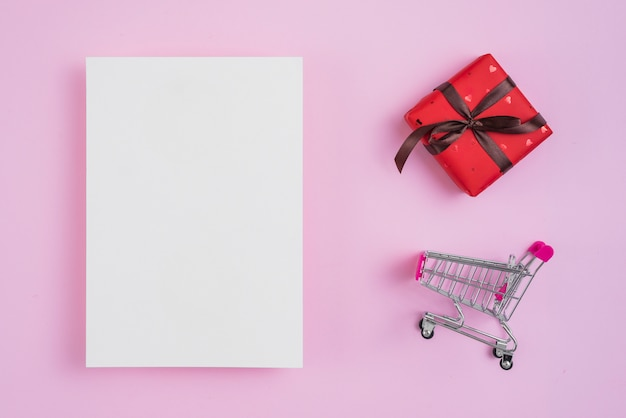 Shopping trolley and gift near paper sheet