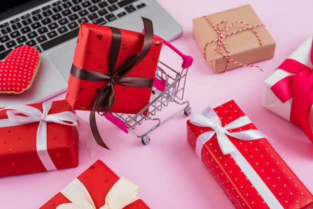 Shopping trolley and gifts near laptop