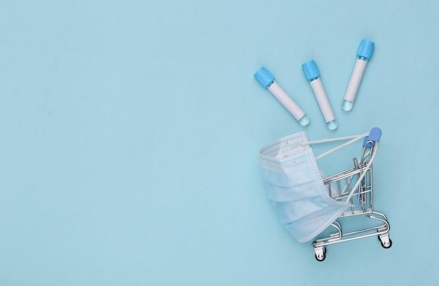 파란색 배경에 테스트 튜브가 있는 의료용 마스크 쇼핑 트롤리. 보건 의료. 평면도