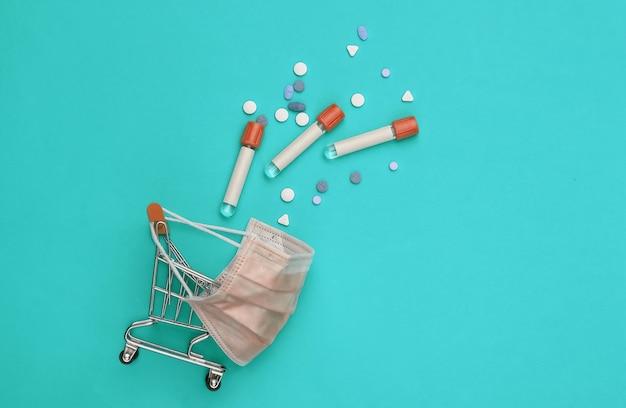 파란색 배경에 시험관이 있는 의료용 마스크 쇼핑 트롤리. 보건 의료