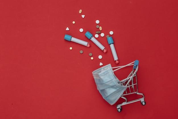 의료용 마스크에 테스트 튜브가 있는 쇼핑 트롤리, 빨간색 배경에 알약. 보건 의료