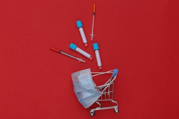 의료용 마스크에 테스트 튜브가 있는 쇼핑 트롤리, 빨간색 배경에 주사기. 보건 의료