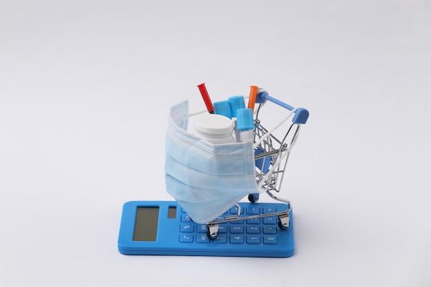 파란색 배경에 시험관, 주사기, 약병, 계산기가 있는 의료용 마스크를 쓴 쇼핑 트롤리. 보건 의료