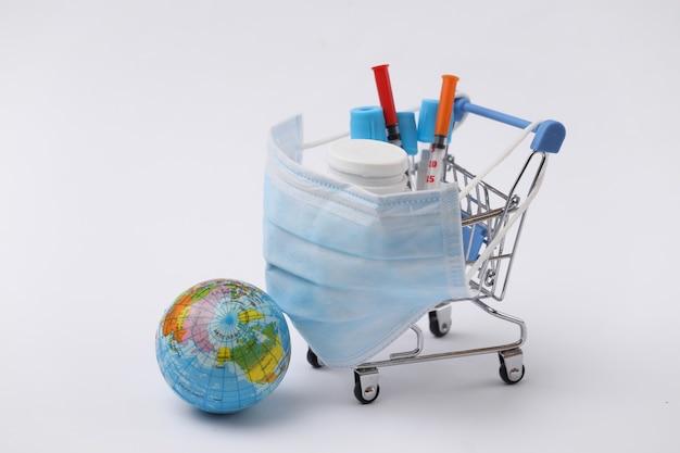 파란색 배경에 테스트 튜브, 주사기, 약 병, 글로브와 함께 의료 마스크에 쇼핑 트롤리. 글로벌 헬스케어