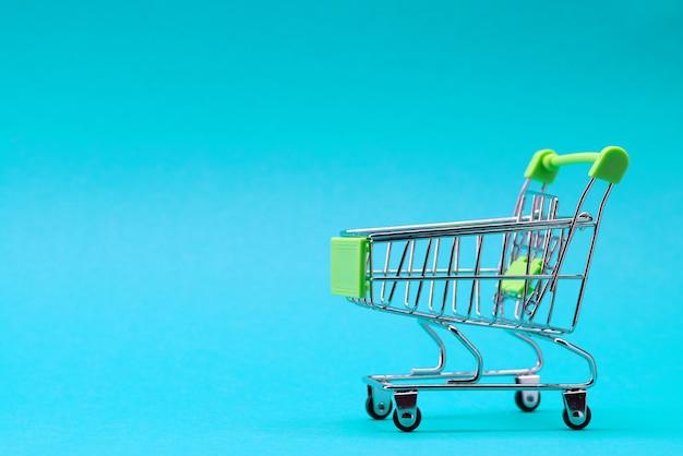 青い背景のショッピングトロリー。緑色。碑文の場所。ショッピングのコンセプト