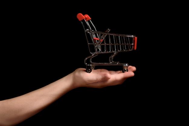 暗い背景に子供の手のひらにショッピングトロリー。ショッピングのコンセプト