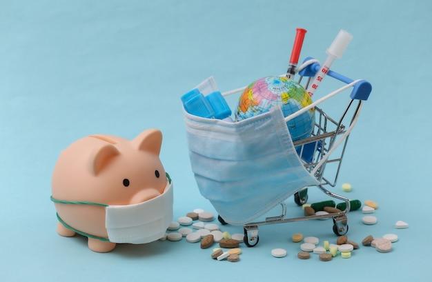 파란색 배경에 시험관, 주사기, 알약, 지구본이 있는 의료용 마스크를 쓴 쇼핑 트롤리, 돼지 저금통. 글로벌 헬스케어