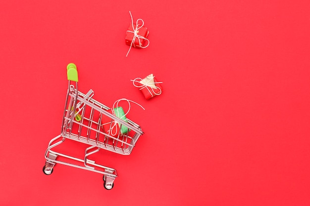 Shopping trolley on a red  with gifts, top view