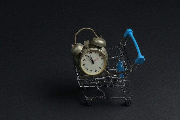 Shopping trolley and retro alarm on black background. 11:55 am. new year.
