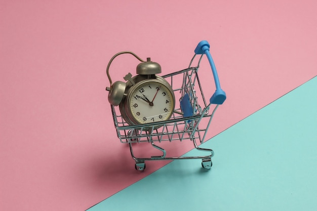 Shopping trolley and retro alarm on pink blue pastel background. 11:55 am. new year.