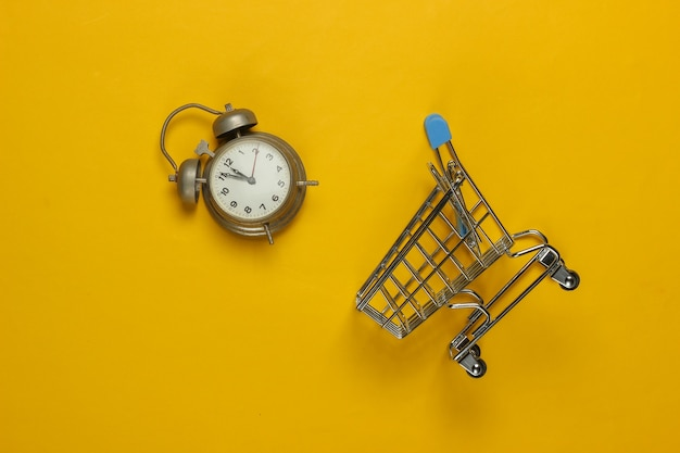 Shopping trolley and retro alarm on yellow background. 11:55 am. new year.