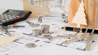 Shopping trolley; stack of coins; keys; paper cut out christmas tree and fountain pen on building plan