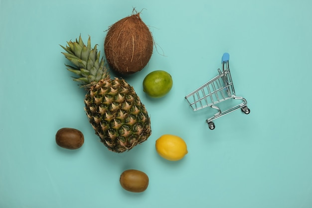 Shopping trolley and tropical fruits on blue background. shopping at the supermarket. healthy food concept. top view