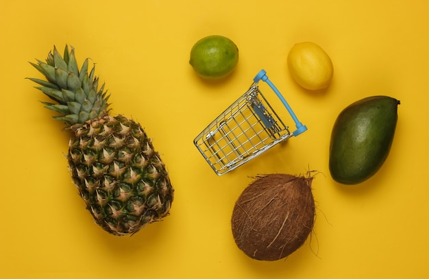 Shopping trolley and tropical fruits on a yellow background. shopping at the supermarket. healthy food concept
