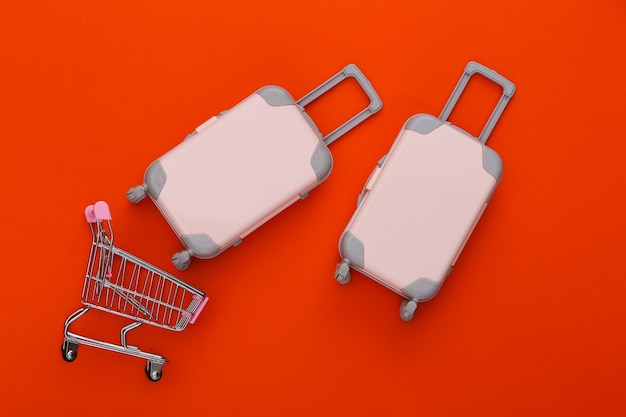Shopping trolley and two toy travel luggage, air plane and ship on orange. travel planning