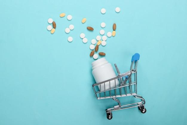 青の丸薬のボトルとショッピングトロリー