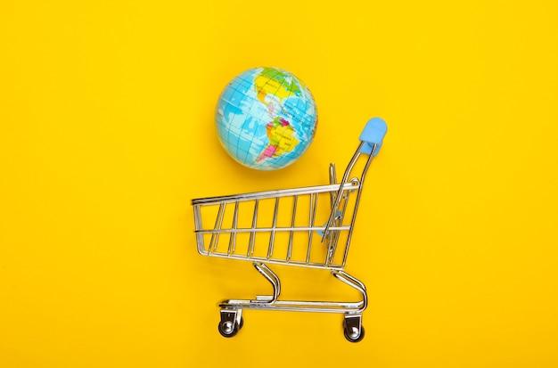 黄色い表面に地球儀が付いたショッピングトロリー