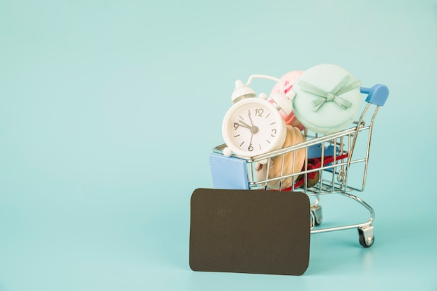 Shopping trolley with alarm clock and macaroons near black tag