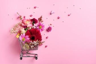 Тележка для покупок с цветами на розовом перламутровом пастельном фоне.