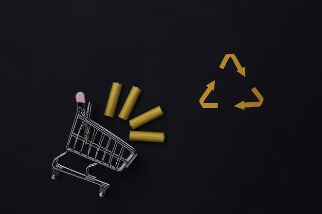 Тележка для покупок с четырьмя желтыми батареями aa и знаком переработанных стрелок на черном фоне. вид сверху