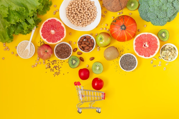 Shopping trolley with fresh organic vegetables, fruits and seeds on yellow background top view