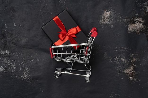 Тележка для покупок с подарочной коробкой и справочным пространством на черном.