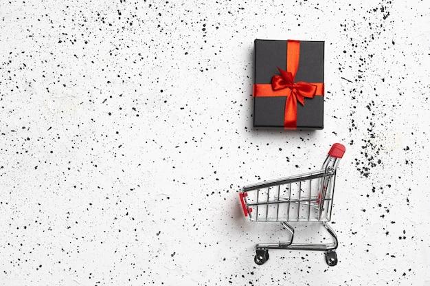 Тележка для покупок с подарочной коробкой и справиться с пространством на белом цементе.