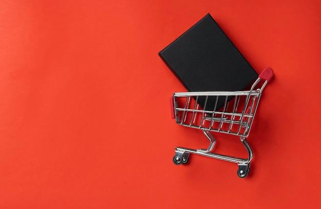 Тележка для покупок с подарочной коробкой на красном фоне