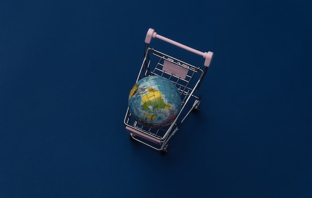 Shopping trolley with globe on classic blue background. global supermarket. color 2020.