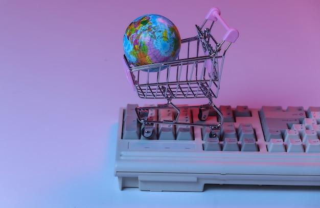 Тележка для покупок с глобусом на старой клавиатуре пк. розовый синий градиент неона, голографический свет. интернет-магазины в стиле ретро