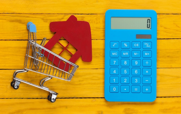 Shopping trolley with house figurine, calculator on yellow wooden