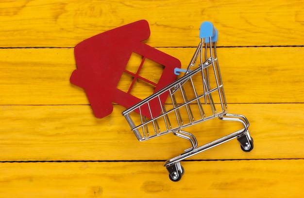黄色の木製の家の置物とショッピングカート