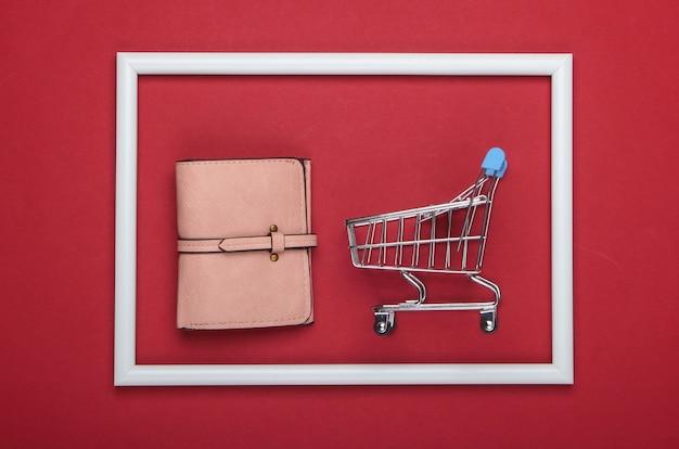 赤い表面の白いフレームの革の財布とショッピングトロリー