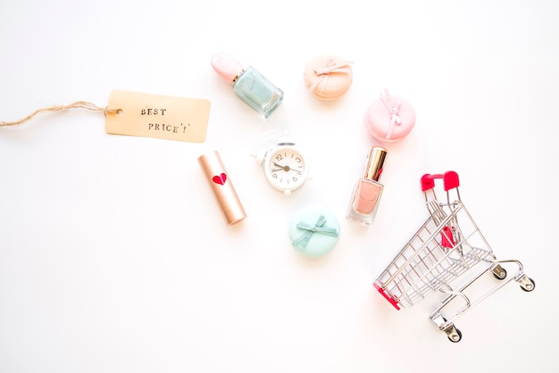 Shopping trolley with little alarm clock, macaroons, sale tag, lipstick and nail polish