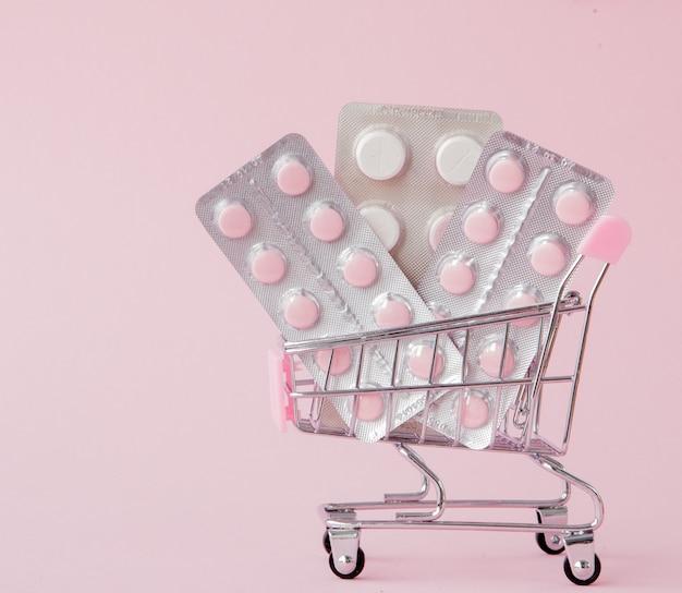 Тележка для покупок с медицинскими таблетками на розовом фоне с копией пространства.