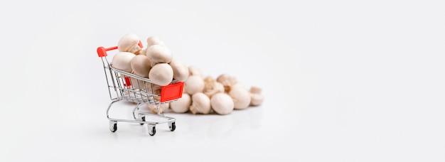 Тележка для покупок с грибами на сером