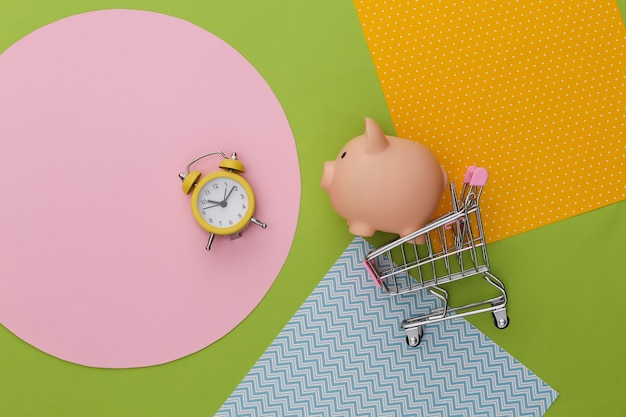 Shopping trolley with piggy bank and alarm clock on creative colorful paper background.