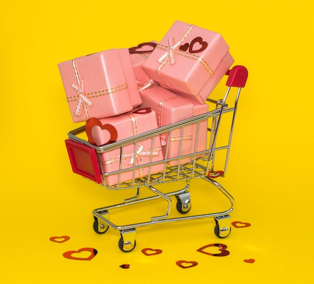 Shopping trolley with pink gifts and red confetti on a yellow background.