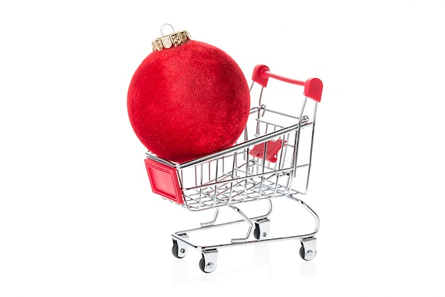 Shopping trolley with red christmas ball isolated on white background