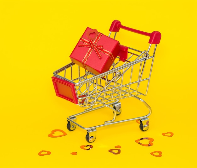 Shopping trolley with red gift and red confetti on a yellow background.