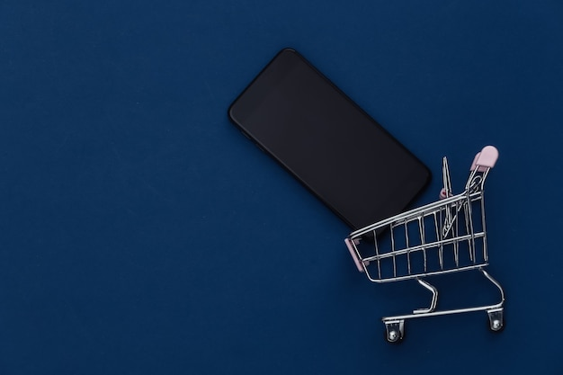 Shopping trolley with smartphone on classic blue background. online shopping. color 2020. top view.