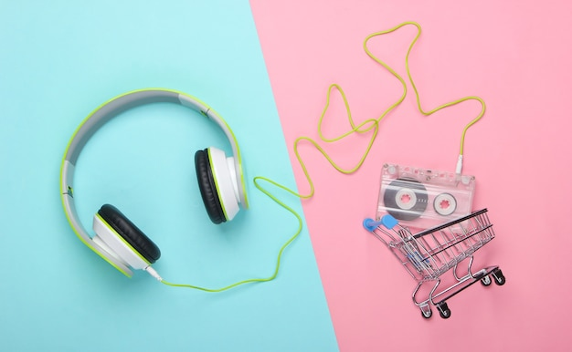 Shopping trolley with stereo headphones and audio cassette on blue pink surface