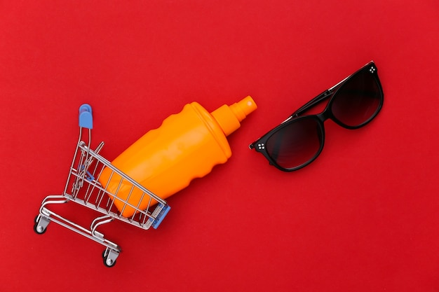 日焼け止めボトル、赤のサングラス付きのショッピングトロリー。皮膚の保護。ビーチでの休暇。