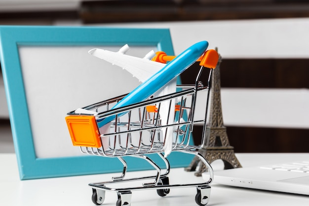 Shopping trolley with toy aircraft on white table close up