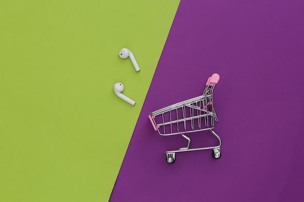 보라색-녹색 배경에 무선 이어폰이 있는 쇼핑 트롤리.